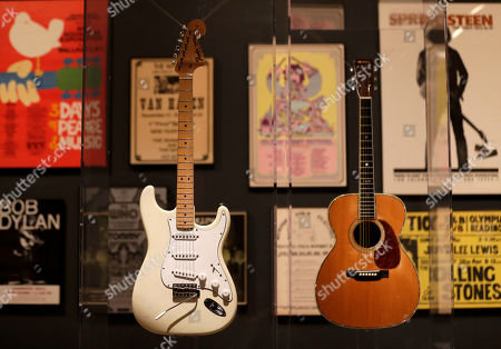 """Guitars used by Jimi Hendrix, left, and Eric Clapton are displayed with concert posters at the exhibit """"Play It Loud: Instruments of Rock & Roll,"""" at the Metropolitan Museum of Art in New York, . The exhibit, which showcases the instruments of rock and roll legends, opens to the public on April 8 and runs until Oct. 1, 2019"""