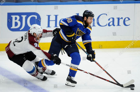 Colorado Avalanche's Gabriel Landeskog (92), of Sweden, reaches for the puck with St. Louis Blues' Ryan O'Reilly (90) during the first period of an NHL hockey game, in St. Louis