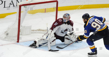 St. Louis Blues' Ryan O'Reilly (90) scores the winning goal in a shootout against Colorado Avalanche's Philipp Grubauer (31), of Germany, in an NHL hockey game, in St. Louis
