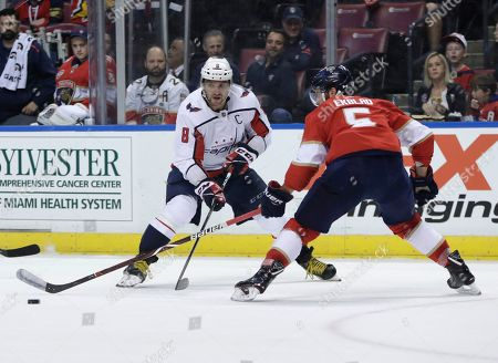 Washington Capitals left wing Alex Ovechkin (8) and Florida Panthers defenseman Aaron Ekblad (5) go for the puck during the first period of an NHL hockey game, in Sunrise, Fla