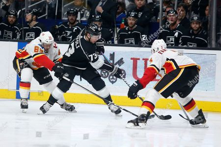 Los Angeles Kings forward Tyler Toffoli (73) vies with Calgary Flames forward Alan Quine (89) and defenseman Oscar Fantenberg (3) during the second period of an NHL hockey game, in Los Angeles