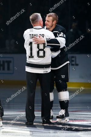 Los Angeles Kings forward Dustin Brown (23) hugs with Hockey Hall of Fame Dave Taylor prior to the NHL hockey game between Los Angeles Kings and Calgary Flames, in Los Angeles. Brown was honored for becoming the Kings franchise leader in games played last week