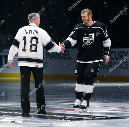 Los Angeles Kings forward Dustin Brown (23) shakes hands with Hockey Hall of Fame Dave Taylor prior to the NHL hockey game between Los Angeles Kings and Calgary Flames, in Los Angeles. Brown was honored for becoming the Kings franchise leader in games played last week