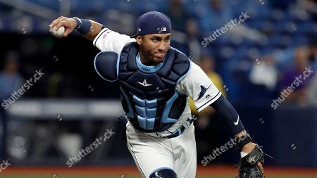Tampa Bay Rays catcher Michael Perez fields a bunt by Colorado Rockies' Garrett Hampson during the third inning of a baseball game, in St. Petersburg, Fla