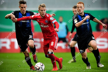 Hamburg's Lewis Holtby (C) in action against Paderborn's Philipp Klement (L) during the German DFB Cup quarter final soccer match between SC Paderborn and Hamburger SV in Paderborn, Germany, 02 April 2019.