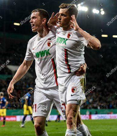 Alfred Finnbogason (R) of Augsburg celebrates with Michael Gregoritsch after scoring the 1-1 during the German DFB Cup quarter final soccer match between FC Augsburg and RB Leipzig in Augsburg, Germany, 02 April 2019.