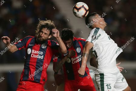 Stock Photo of Gustavo Gomez of Brazil's Palmeiras heads the ball challenged by Fabricio Coloccini of Argentina's San Lorenzo during a Copa Libertadores Group F soccer match in Buenos Aires, Argentina