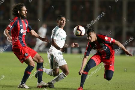 Marcelo Herrera of Argentina's San Lorenzo, right, and Dudu of Brazil's Palmeiras vie for the ball as Fabricio Coloccini of Argentina's San Lorenzo, left, looks on during a Copa Libertadores Group F soccer match in Buenos Aires, Argentina
