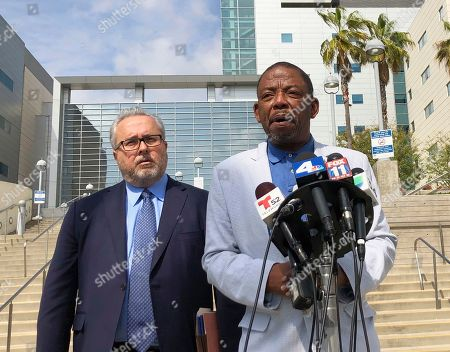 Attorneys Carl Douglas, right, with David Lira, talks to reporters outside Los Angeles County-USC Medical Center, . They represent Rafael Reyna, on life support in the hospital following a weekend assault outside Dodger Stadium, saying the team hasn't done enough to improve security since a similar attack eight years ago. Police are searching for a man who punched Reyna during an argument following Friday night's marathon six-hour game between the Dodgers and the Arizona Diamondbacks