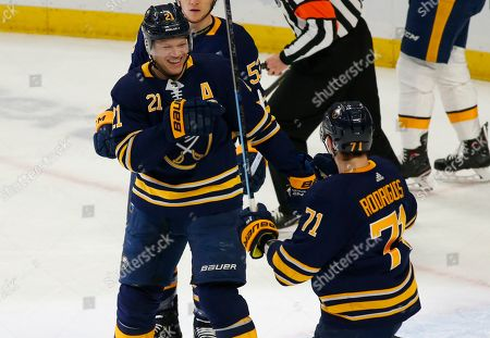 Buffalo Sabres forwards Kyle Okposo (21) and Evan Rodrigues (71) celebrate a goal during the first period of an NHL hockey game against the Nashville Predators, in Buffalo, N.Y