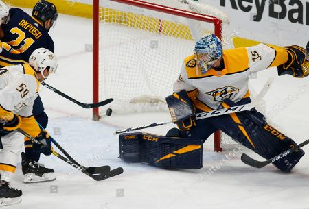 Buffalo Sabres forward Kyle Okposo (21) puts the puck past Nashville Predators goalie Pekka Rinne (35) during the first period of an NHL hockey game, in Buffalo, N.Y