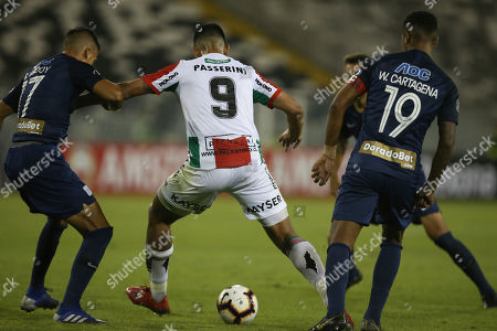 Lucas Passerini of Chile's Palestino, center, fights the ball with Peru's Alianza Lima Gonzalo Godoy, left, and Wilder Cartagena, during a Copa Libertadores soccer match in Santiago, Chile