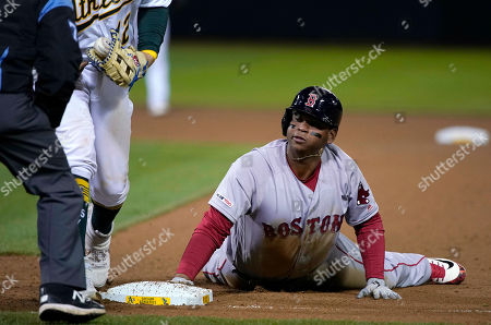 Stock Picture of Boston Red Sox's Rafael Devers slides back safely to first base in front of the tag from Oakland Athletics designated hitter Kendrys Morales, left, during the fourth inning of a baseball game in Oakland, Calif