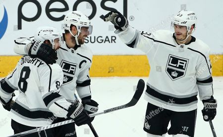 Los Angeles Kings defenseman Drew Doughty (8) celebrates his empty-net goal against the Arizona Coyotes with Kings center Anze Kopitar, middle, and right wing Dustin Brown (23) during the third period of an NHL hockey game, in Glendale, Ariz. The Kings defeated the Coyotes 3-1