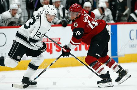 Arizona Coyotes right wing Michael Grabner (40) and Los Angeles Kings right wing Dustin Brown (23) get tangled up during the first period of an NHL hockey game, in Glendale, Ariz