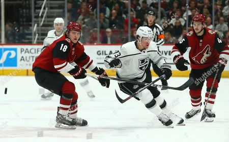 Los Angeles Kings right wing Tyler Toffoli (73) battles with Arizona Coyotes center Christian Dvorak (18) and Coyotes right wing Josh Archibald (45) as the puck zips past all of them during the first period of an NHL hockey game, in Glendale, Ariz