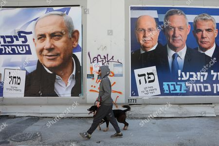 A man walks with his dog between election campaign billboards of Prime Minister and leader of the Likud party Benjamin Netanyahu (L) and leaders of the Blue and White party Benny Gantz (2-R) and Yair Lapid (3-R) and Moshe Ya'alon (R), in Tel Aviv, Israel, 03 April 2019. Israelis will go to the polls on 09 April.