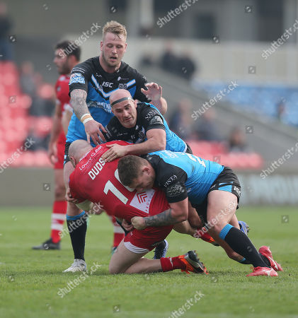 Josh Wood of Salford Red Devils is floored by Joe Westerman of Hull FC and Jordan Lane of Hull FC and Danny Houghton of Hull FC