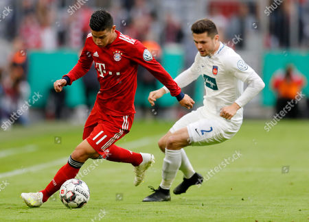 Bayern's James Rodriguez (L) in action against Heidenheim's Marnon Busch (R) during the German DFB Cup quarter final soccer match between FC Bayern Munich and 1. FC Heidenheim in Munich, Germany, 03 April 2019.