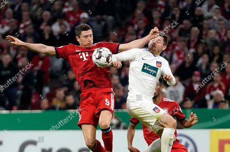 Heidenheim's Marnon Busch (R) touches with the hand the ball against Bayern's Robert Lewandowski during the German DFB Cup quarter final soccer match between FC Bayern Munich and 1. FC Heidenheim in Munich, Germany, 03 April 2019.