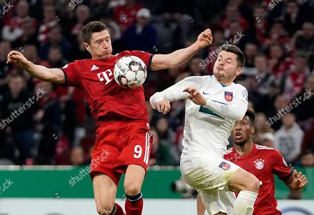 Bayern's Robert Lewandowski (L) in action against Heidenheim's Marnon Busch (R) during the German DFB Cup quarter final soccer match between FC Bayern Munich and 1. FC Heidenheim in Munich, Germany, 03 April 2019.