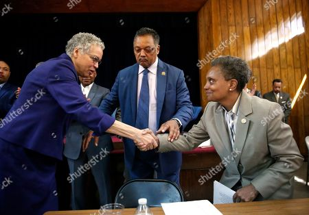 Chicago Mayor-elect Lori Lightfoot, right, shakes hands with her opponent Toni Preckwinkle as Rev. Jesse Jackson look on during a press conference at the Rainbow PUSH organization, Wednesday morning, in Chicago