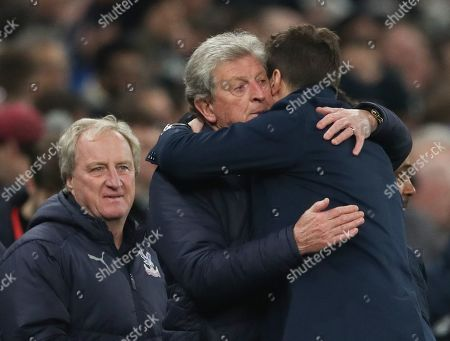 Tottenham Hotspur manager Mauricio Pochettino hugs Crystal Palace manager Roy Hodgson watched by assistant Ray Lewington (left)