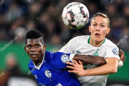 Bremen's Ludwig Augustinsson, right, and Schalke's Breel Embolo challenge for the ball during the German soccer cup, DFB Pokal, quarterfinal match between FC Schalke 04 and Werder Bremen in Gelsenkirchen, Germany