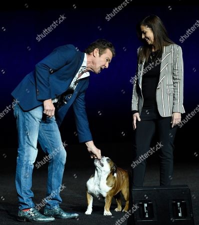 """Dennis Quaid, Gail Mancuso. Dennis Quaid, left, a cast member in the upcoming film """"A Dog's Journey,"""" attends to his dog as the film's director Gail Mancuso looks on during the Universal Pictures presentation at CinemaCon 2019, the official convention of the National Association of Theatre Owners (NATO) at Caesars Palace, in Las Vegas"""