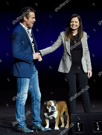 """Stock Picture of Dennis Quaid, Gail Mancuso. Dennis Quaid, left, a cast member in the upcoming film """"A Dog's Journey,"""" and the film's director Gail Mancuso are joined by Quaid's dog during the Universal Pictures presentation at CinemaCon 2019, the official convention of the National Association of Theatre Owners (NATO) at Caesars Palace, in Las Vegas"""
