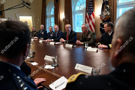 President Donald Trump, center, flanked by acting Defense Secretary Patrick Shanahan, left, and Chairman of the Joint Chiefs of Staff Gen. Joseph Dunford, right, speaks during a meeting with military leaders in the Cabinet Room of the White House in Washington