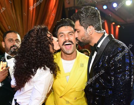 Bollywood actors Tapasee Pannu and Vicky Kaushal kiss actor Ranveer Singh