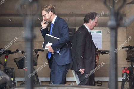 Conservative MPs Oliver Letwin (R) and Tobias Ellwood pass each other in Parliament