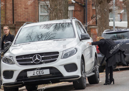 Stock Picture of Lauryn Goodman hides getting out of the passenger seat of her sister Chloe Goodman's car as they leave Hove Trial centre after Lauryn received a suspended sentence