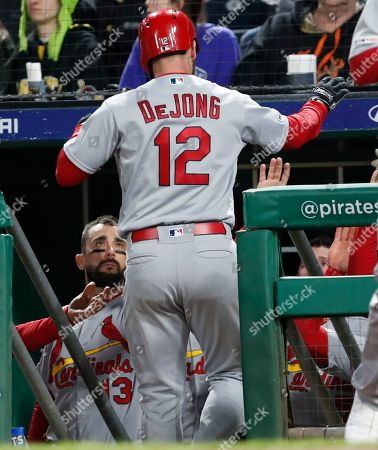 Paul DeJong, Matt Carpenter. St. Louis Cardinals' Paul DeJong (12) is greed by Matt Carpenter, left and other teammates in the dugout after hitting a solo home run in the seventh inning of a baseball game against the Pittsburgh Pirates, in Pittsburgh
