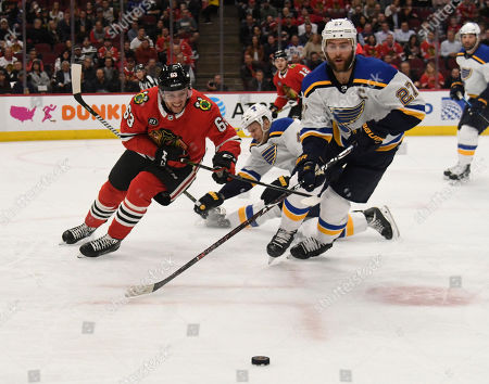 St. Louis Blues defenseman Alex Pietrangelo (27) and Chicago Blackhawks defenseman Carl Dahlstrom (63) go for the puck during the first period of an NHL hockey game, in Chicago