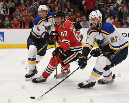 Chicago Blackhawks defenseman Carl Dahlstrom (63) and St. Louis Blues' Alex Pietrangelo (27) and Carl Gunnarsson (4) go for the puck during the first period of an NHL hockey game, in Chicago