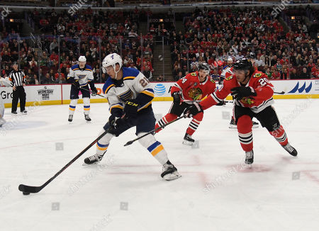St. Louis Blues center Tyler Bozak (21) is defended by Chicago Blackhawks left wing Brandon Saad (20) during the first period of an NHL hockey game, in Chicago