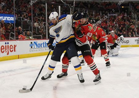St. Louis Blues left wing Pat Maroon, left, fends off Chicago Blackhawks defenseman Carl Dahlstrom during the second period of an NHL hockey game, in Chicago