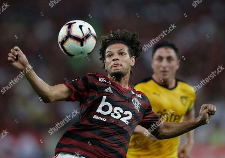 Stock Photo of Willian of Brazil's Flamengo goes for the ball as Cristian Rodriguez of Uruguay's Penarol looks on from behind during a Copa Libertadores soccer match at Maracana stadium in Rio de Janeiro, Brazil