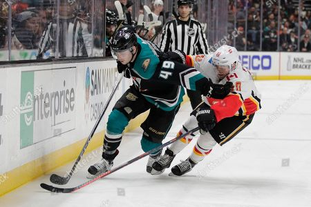Max Jones, Derek Ryan. Anaheim Ducks' Max Jones, left, moves the puck past Calgary Flames' Derek Ryan during the second period of an NHL hockey game, in Anaheim, Calif