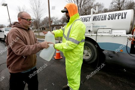 In this photo from, Paul Otto, right, an employee of Omaha's Municipal Utilities District, hands Jim Mitchell of Glenwood, Iowa, jugs of water he had filled from MUD's emergency water supply tanker, in Glenwood, Iowa. Several communities along the Missouri River continue to struggle to restore drinking water service weeks after massive flooding disrupted life in the towns and caused significant damage