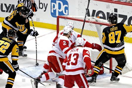 Pittsburgh Penguins' Phil Kessel (81) puts a rebound behind Detroit Red Wings goaltender Jimmy Howard for a goal in the first period of an NHL hockey game in Pittsburgh