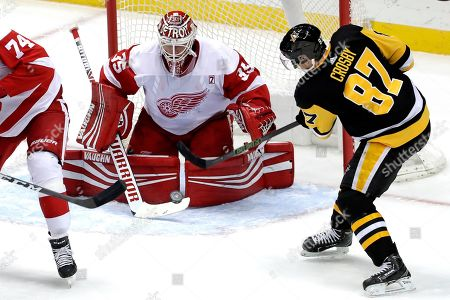 Detroit Red Wings goaltender Jimmy Howard stops a shot by Pittsburgh Penguins' Sidney Crosby (87) in the first period of an NHL hockey game in Pittsburgh