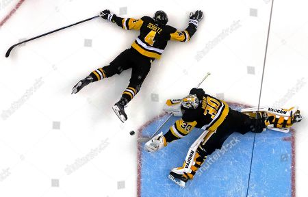 Stock Photo of Detroit Red Wings' Martin Frk (42) can't get a shot past Pittsburgh Penguins goaltender Matt Murray (30) and defenseman Justin Schultz (4) in the third period of an NHL hockey game in Pittsburgh, . The Penguins won 4-1