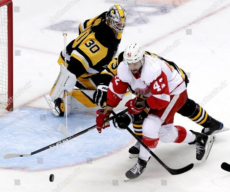 Matt Murray, Martin Frk, Jack Johnson. Detroit Red Wings' Martin Frk (42) can't get his stick on a loose puck behind Pittsburgh Penguins goaltender Matt Murray (30) with Jack Johnson (73) defending during the first period of an NHL hockey game in Pittsburgh