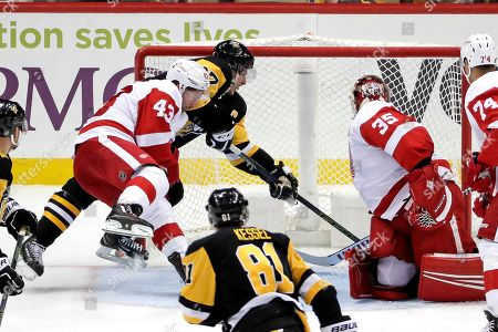 Sidney Crosby, Jimmy Howard, Darren Helm. Pittsburgh Penguins' Sidney Crosby, center rear, knocks a rebound behind Detroit Red Wings goaltender Jimmy Howard (35) for a goal with Darren Helm (43) defending during the third period of an NHL hockey game in Pittsburgh, . The Penguins won 4-1