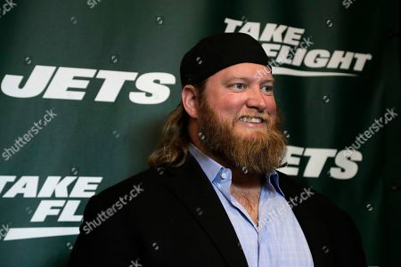 Former New York Jets center Nick Mangold poses for photographers on the green carpet ahead of an event unveiling the team's new NFL football uniforms, in New York