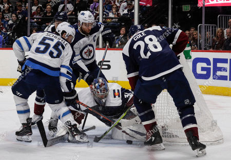 Stock Image of Winnipeg Jets center Mark Scheifele (55) pushes the puck past Colorado Avalanche goaltender Philipp Grubauer (31) for a goal during the first period of an NHL hockey game in Denver