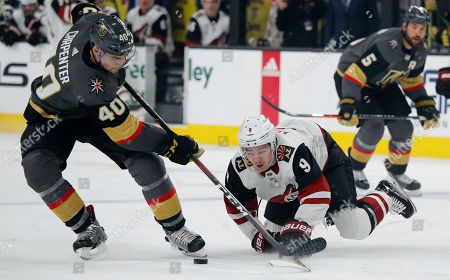 Vegas Golden Knights center Ryan Carpenter (40) and Arizona Coyotes center Clayton Keller (9) vie for the puck during the first period of an NHL hockey game, in Las Vegas